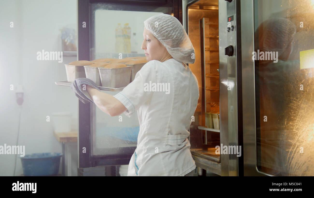 Hornea femenino en cocina comercial - Extrae el pan del horno Imagen De Stock