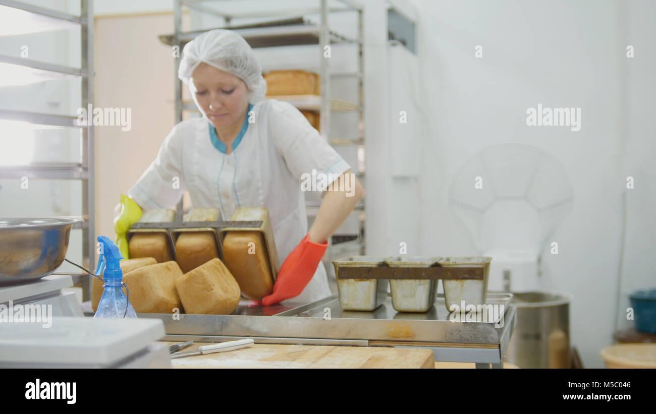 Hornea pan femenino en cocina comercial Imagen De Stock