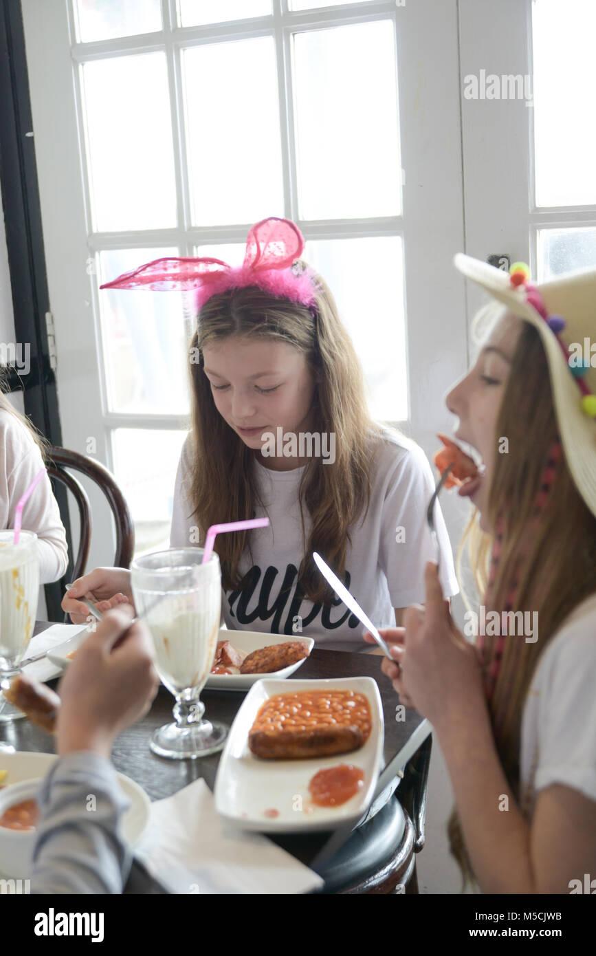 Dos niños están sentados en la mesa del partido de comer alimentos fritos y beber batidos- hay globos Imagen De Stock