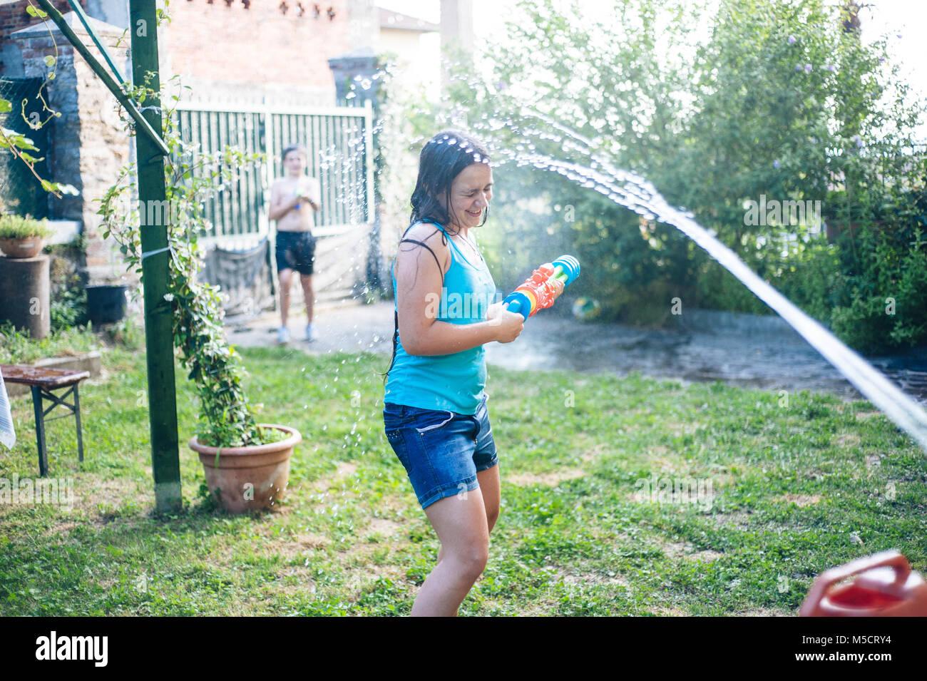 Los niños juegan en el jardín con pistolas y rifles de agua en un día soleado de verano teniendo Imagen De Stock