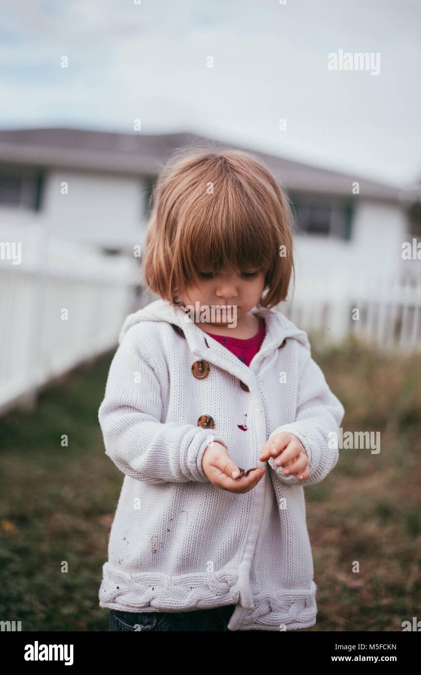 Un niño niña tiene en sus manos un gusano en un frío día de primavera. Imagen De Stock