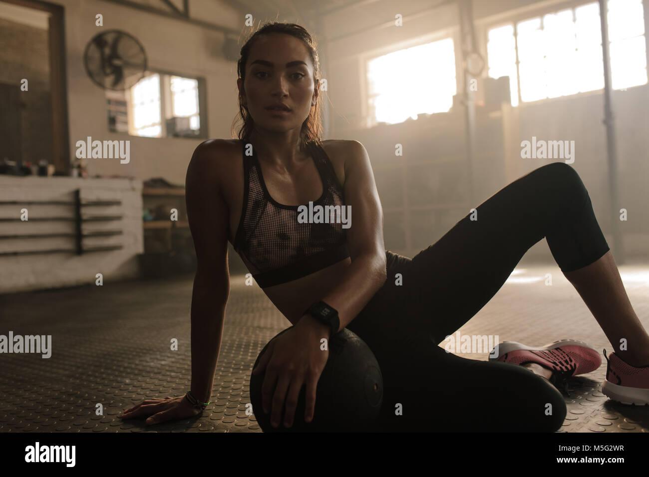 Mujer joven sentado en el piso del gimnasio con balón medicinal tras la sesión de ejercicio. Mujeres tomando Imagen De Stock