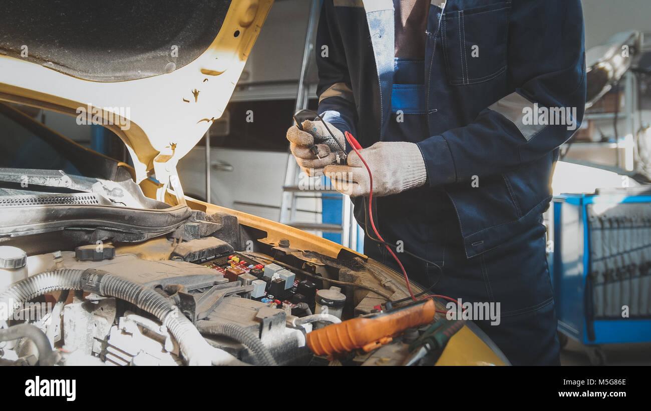 Mecánico que trabaja con el voltímetro: Coche eléctrico - cableado eléctrico Imagen De Stock
