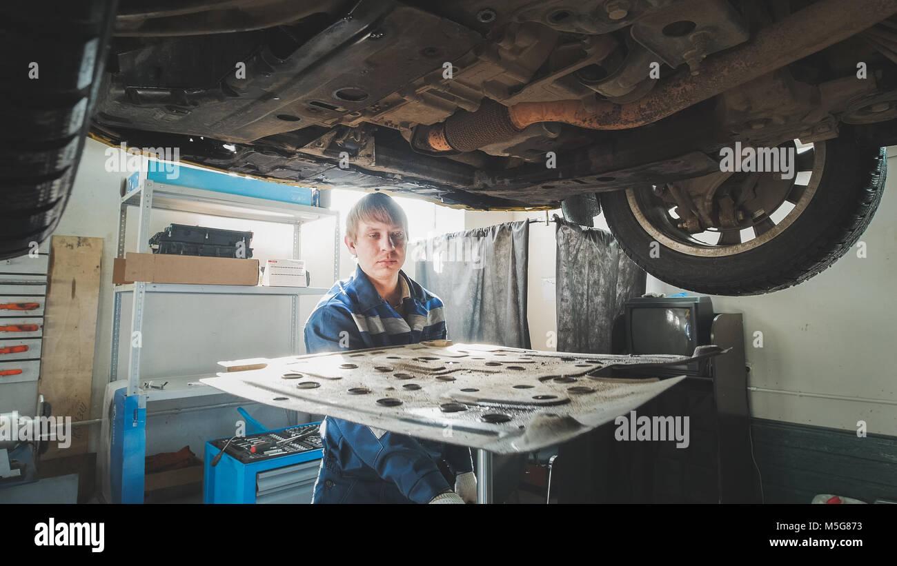 En el trabajo - mecánica del automóvil titular inferior bajo levantó auto Imagen De Stock
