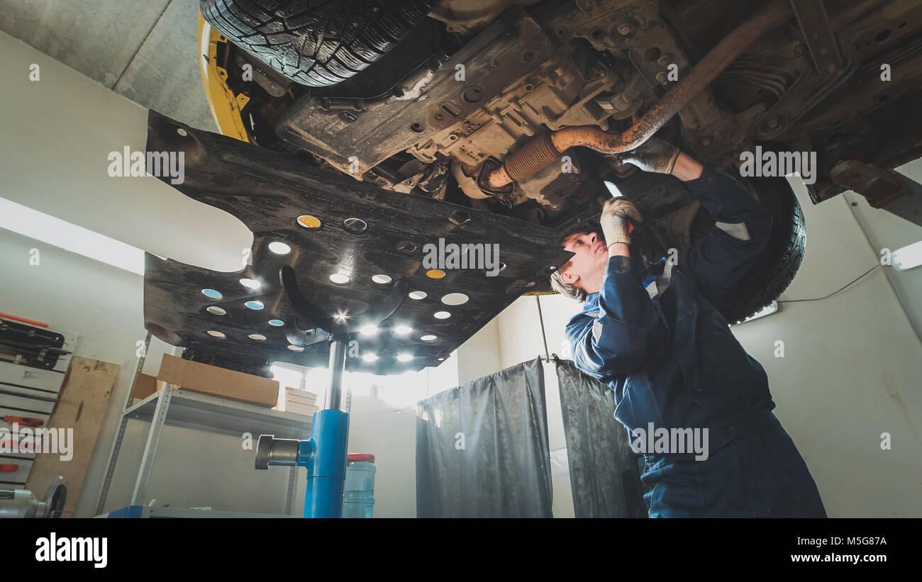 Trabajador mecánico comprueba la parte inferior del coche - servicio automotriz Imagen De Stock