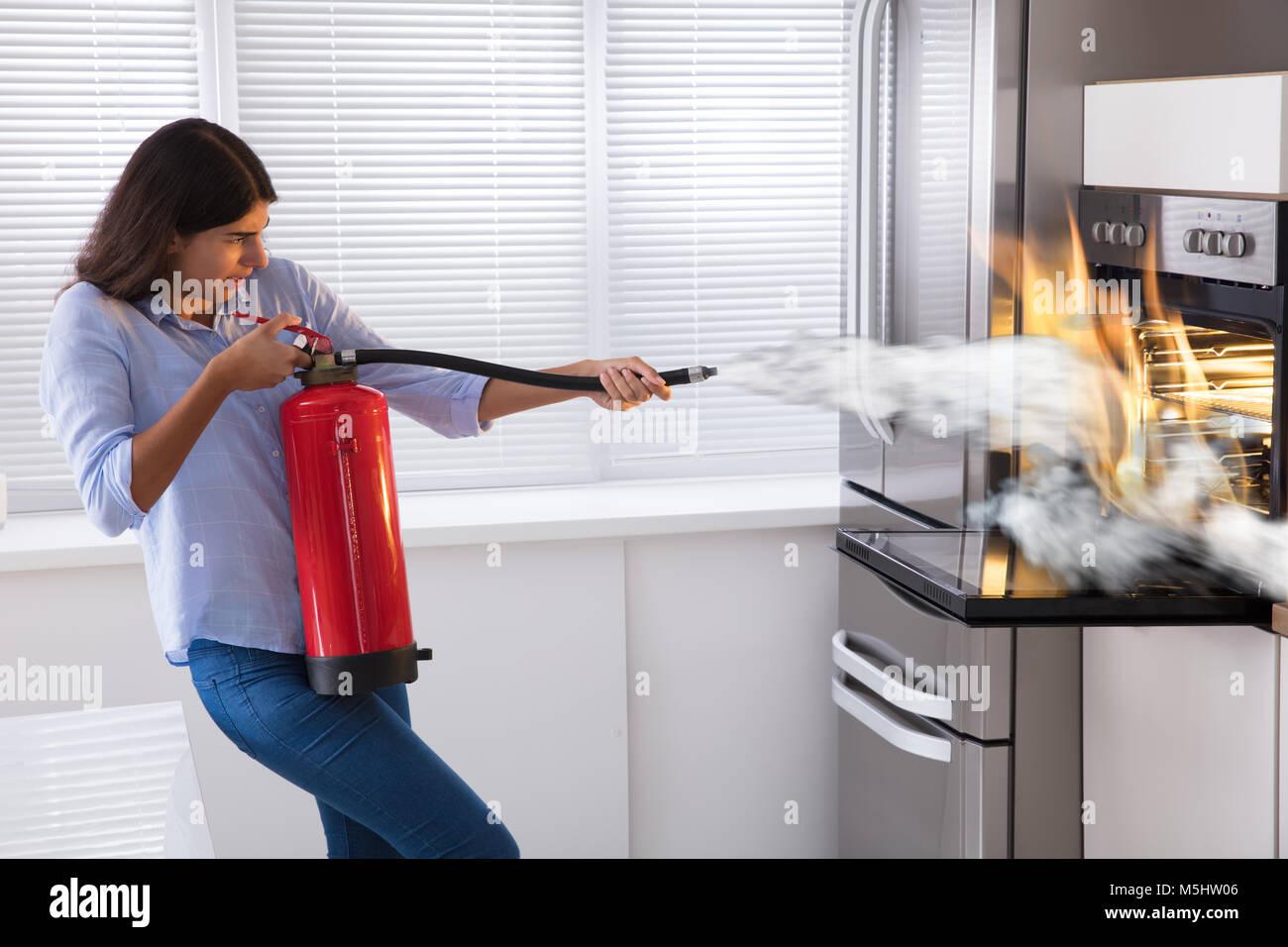 Mujer joven con extintor de incendios para apagar el fuego del horno en casa foto imagen de - Extintor para casa ...