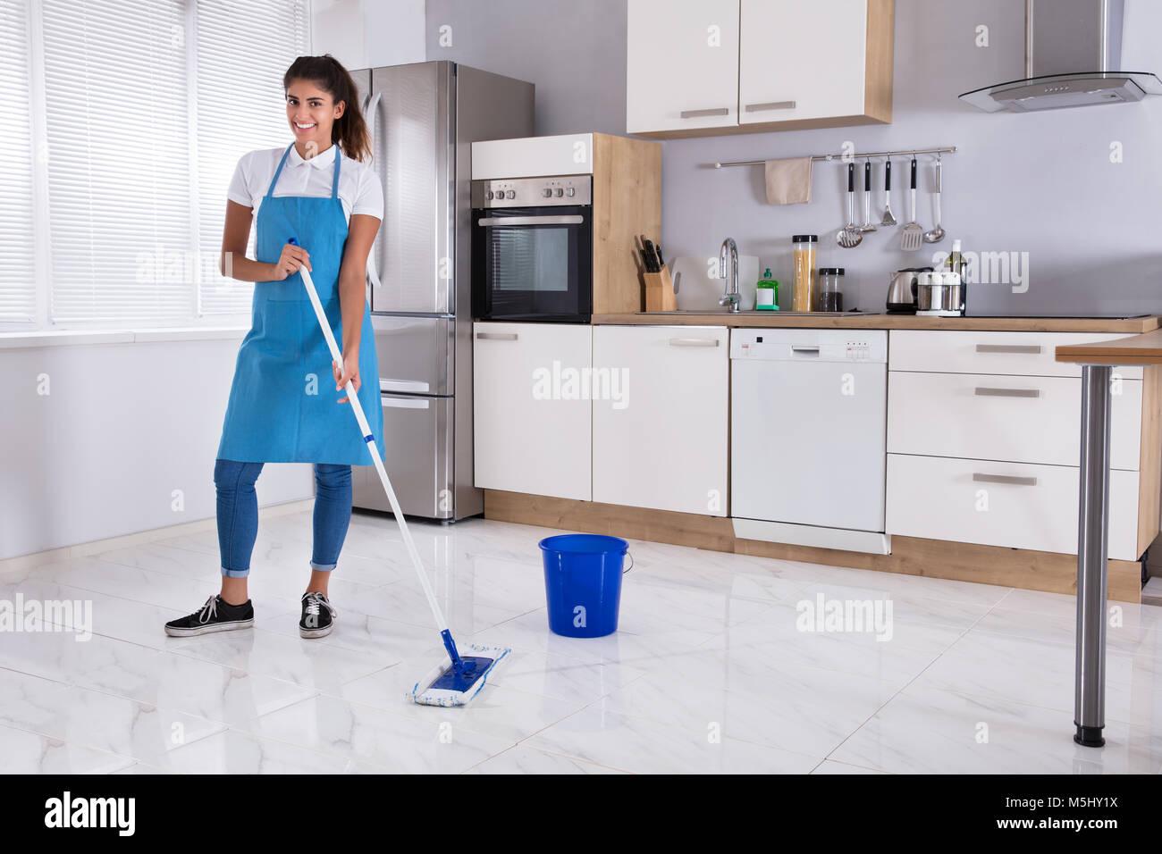 Mujer Alegre Y Limpiar El Piso Con El Mop En Cocina En Casa Fotografía De Stock Alamy