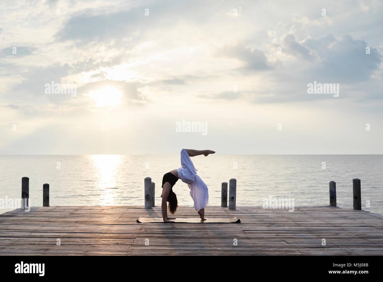 Instructor de Yoga hacer yoga contra la puesta de sol y mar. Kep, Camboya. Imagen De Stock