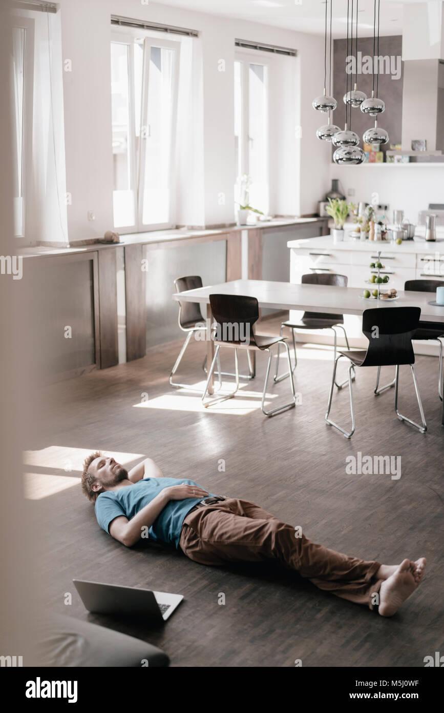 Hombre tumbado en el suelo en un loft de descanso Imagen De Stock