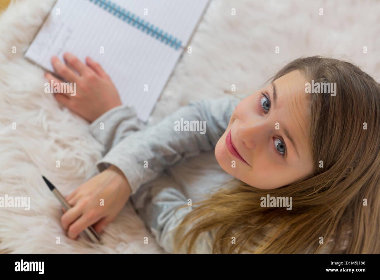 Retrato de niña sonriente tumbado en el suelo con un lápiz y un folleto Foto de stock