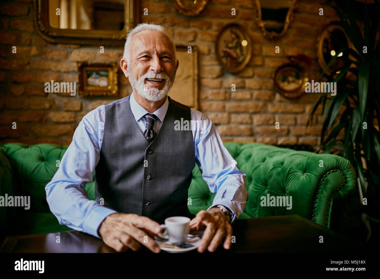 Senior elegante retrato de hombre sentado en el sofá en una cafetería sonriendo Foto de stock