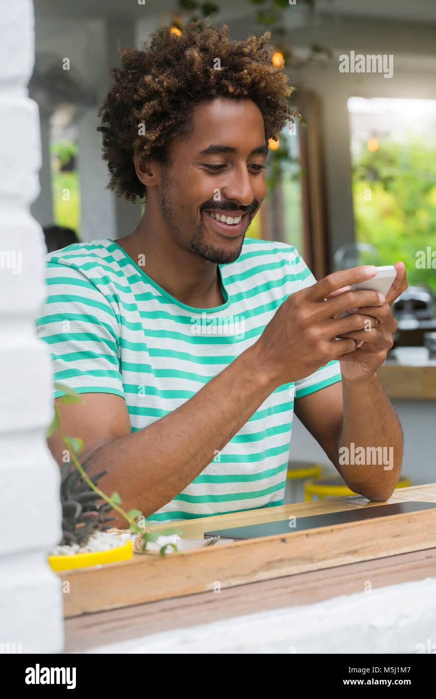Hombre sonriente al comprobar su smartphone en la barra de una cafetería Imagen De Stock