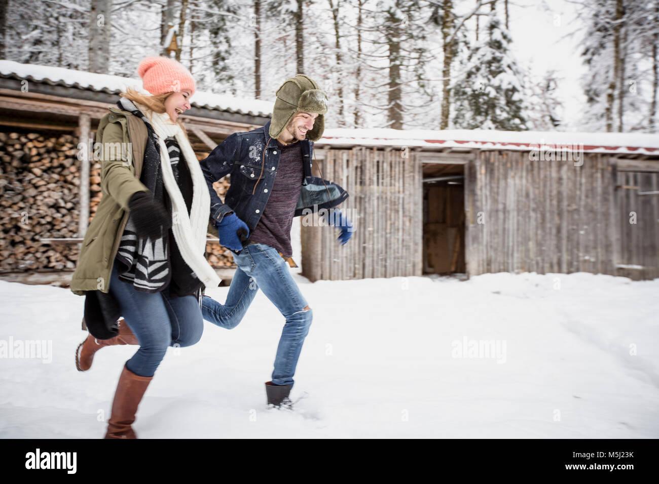 Pareja feliz corriendo delante del montón de madera al aire libre en invierno Imagen De Stock