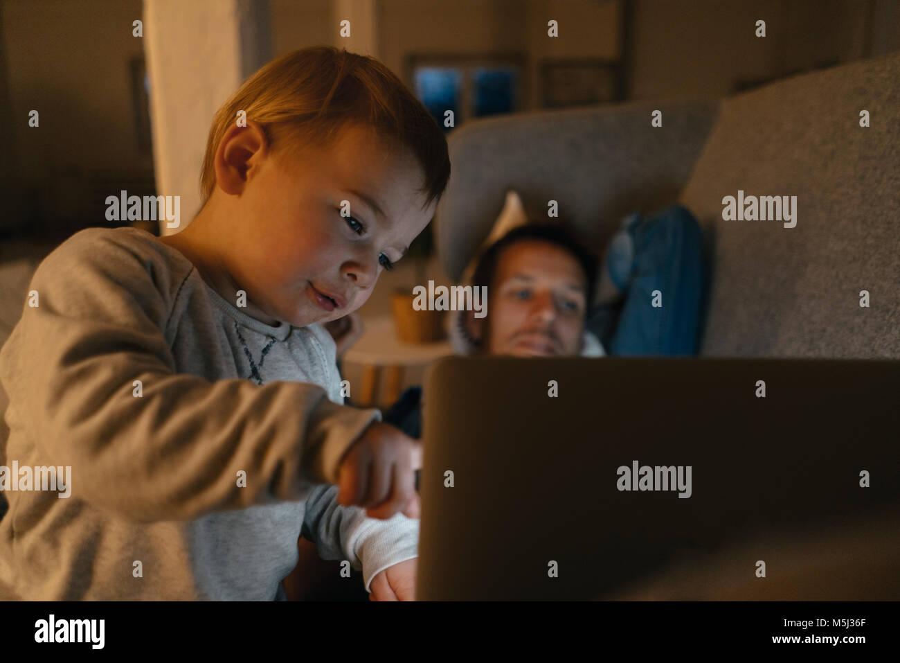 Litle chica con padres mirando el portátil en el sofá en la oscuridad Foto de stock