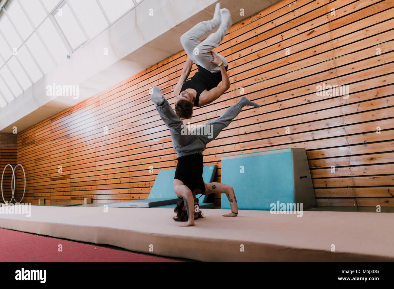 Dos hombres haciendo acrobacias en el gimnasio Imagen De Stock