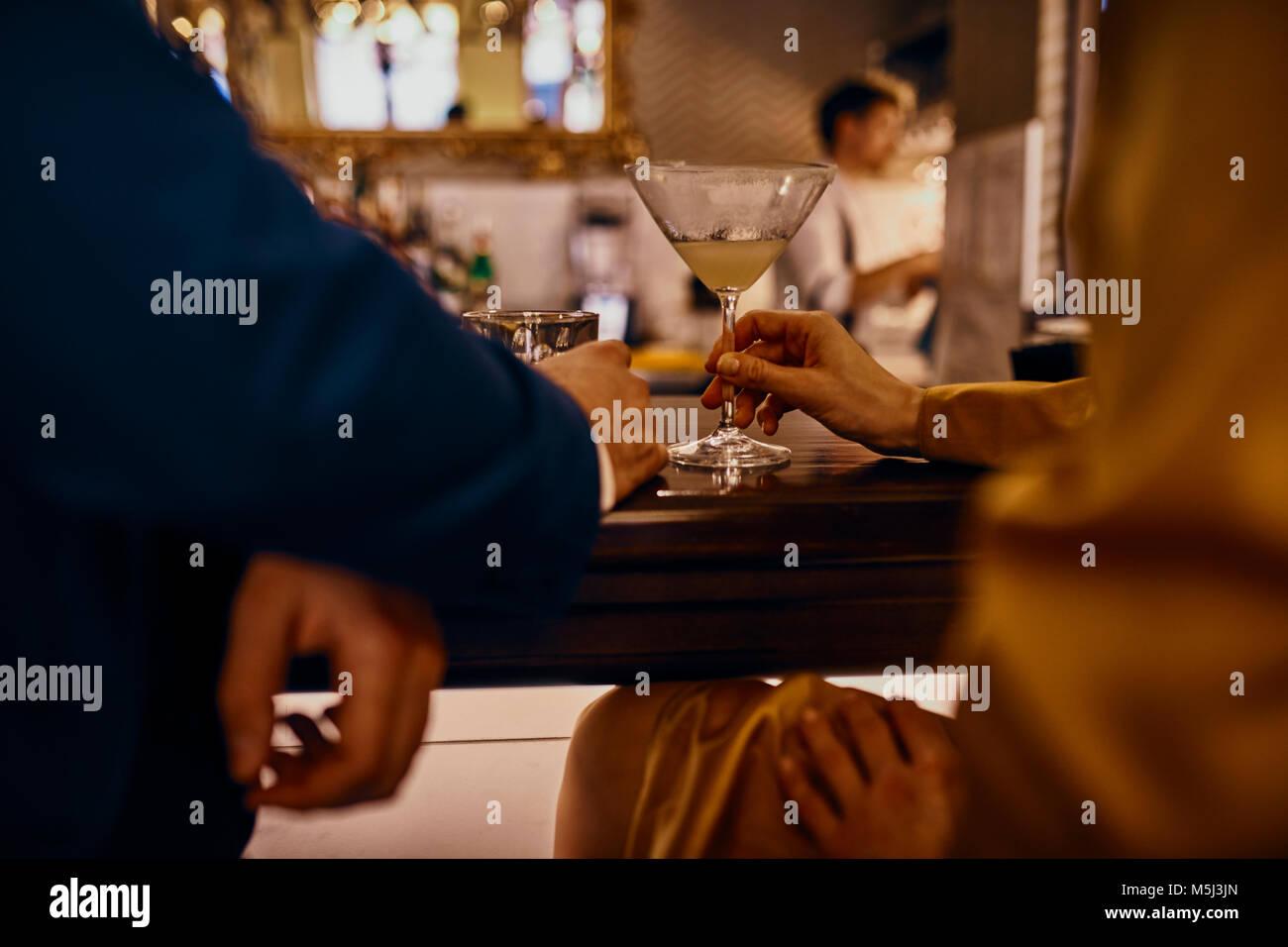 Cerca de la elegante pareja tomando una copa en el mostrador en un bar. Imagen De Stock