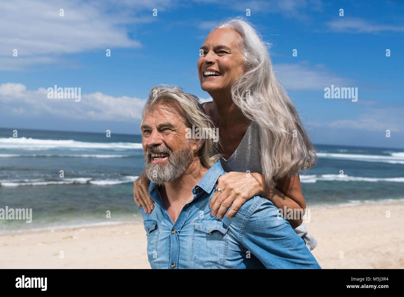 Guapo pareja senior divirtiéndose en la playa. Imagen De Stock