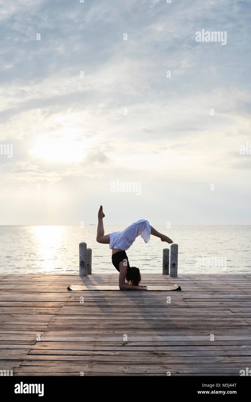 Instructor de Yoga en Pincha mayurasana con patas de ciervo en un puente de madera contra la puesta de sol y mar. Imagen De Stock
