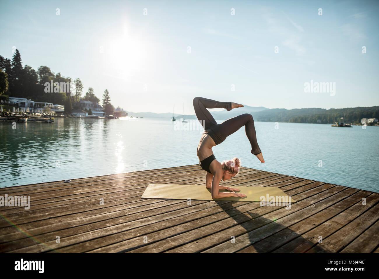 Mujer practicando yoga en muelle en un lago Imagen De Stock