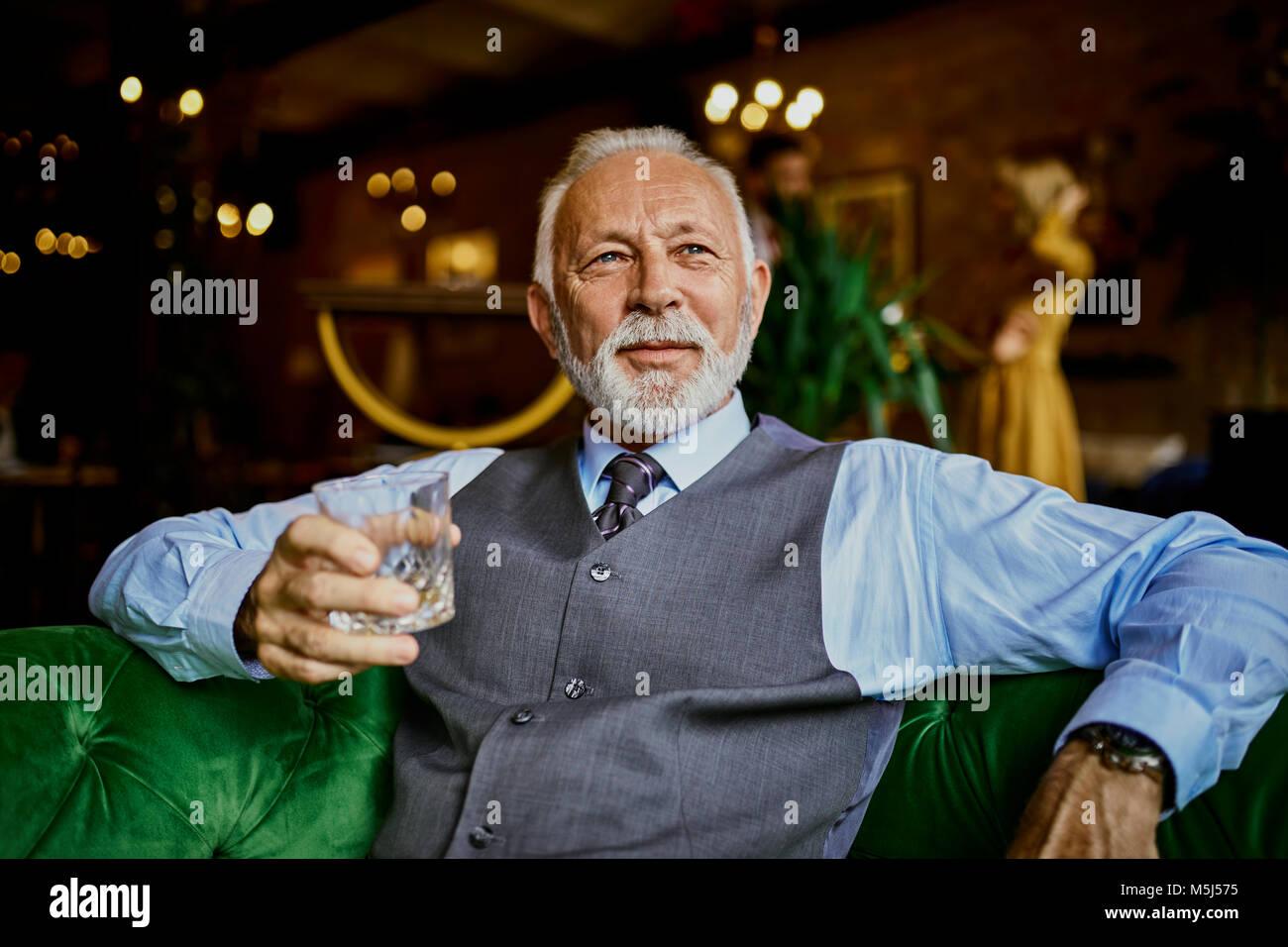 Senior elegante retrato de hombre sentado en el sofá en un bar celebración tumbler Imagen De Stock