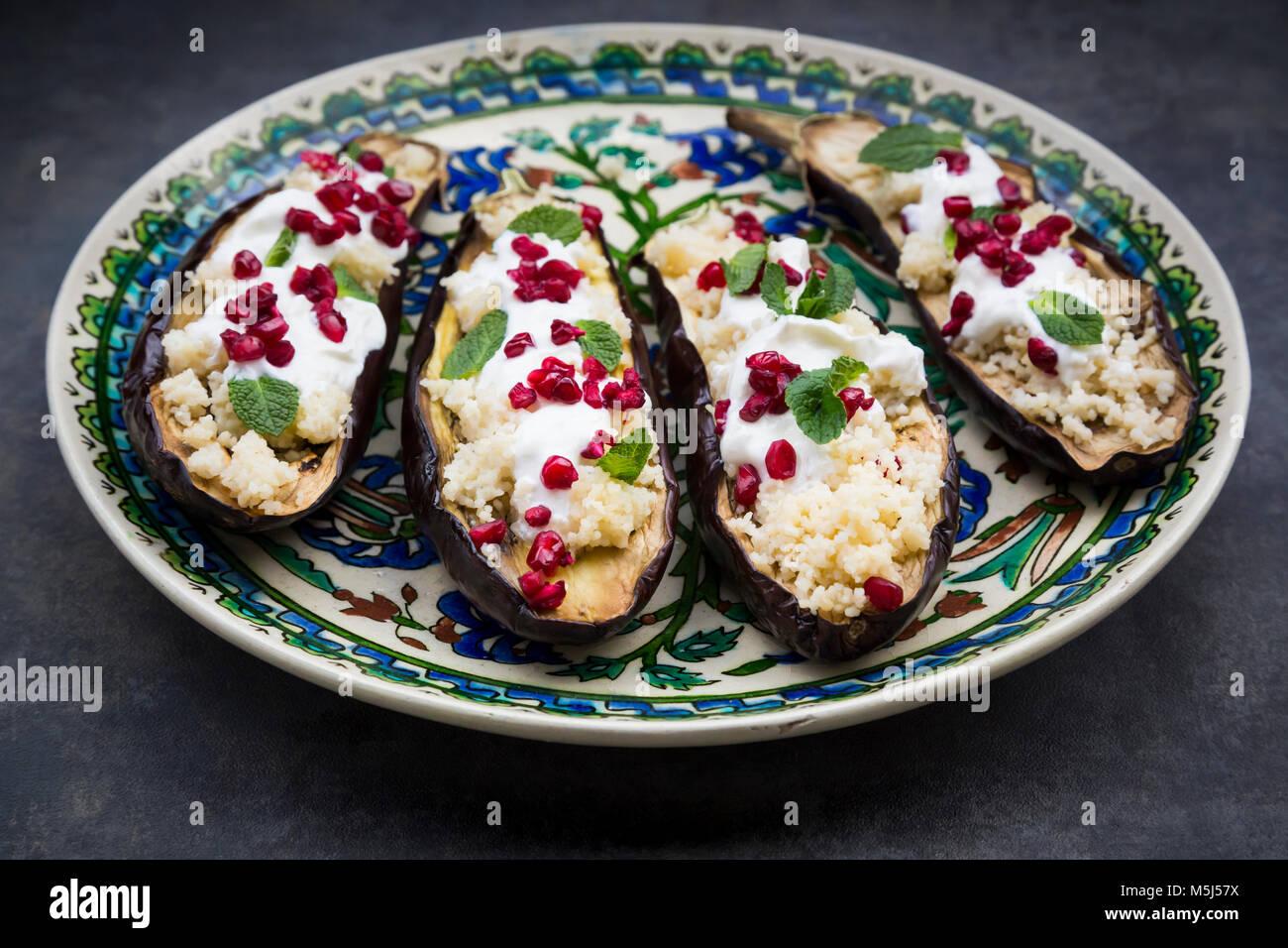 Berenjenas rellenas, cuscús, salsa de yogur, menta y semillas de granada Imagen De Stock
