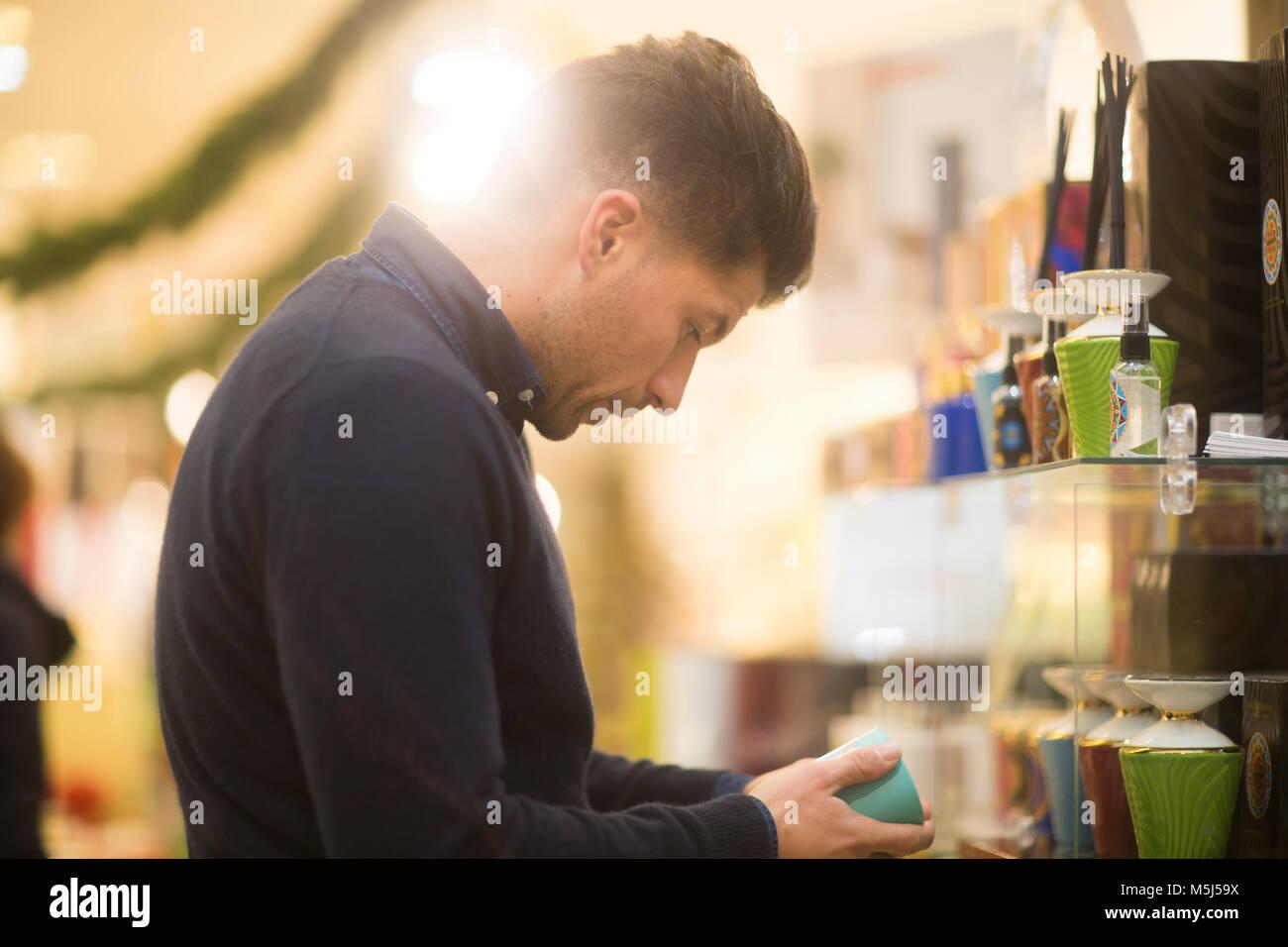 Hombre mirando incierto para regalo de Navidad en una tienda Imagen De Stock