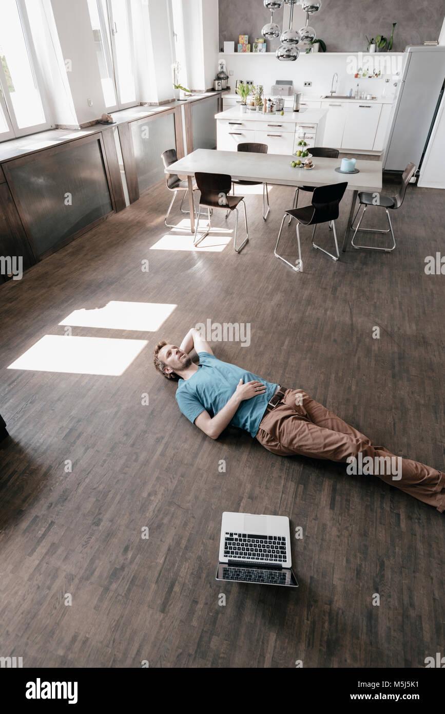 Pensativo hombre tumbado en el suelo en un loft Imagen De Stock