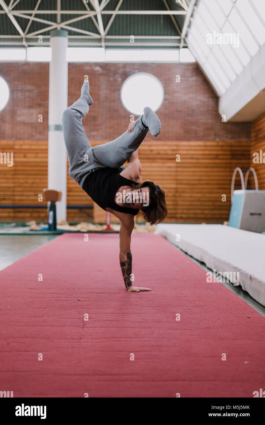 Joven haciendo ejercicio en el gimnasio acrobático Imagen De Stock