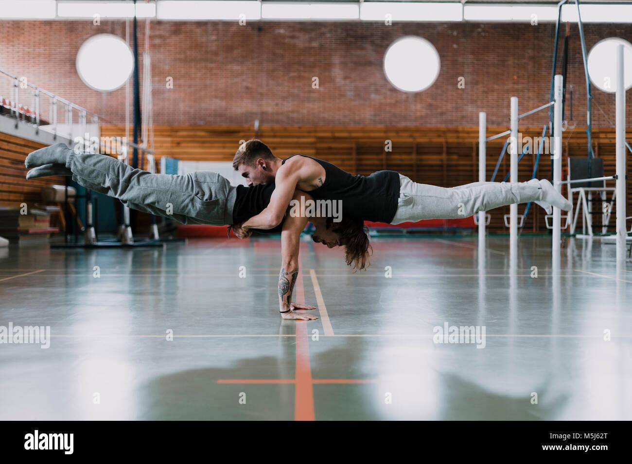 Dos hombres haciendo acrobacias en el gimnasio Foto de stock