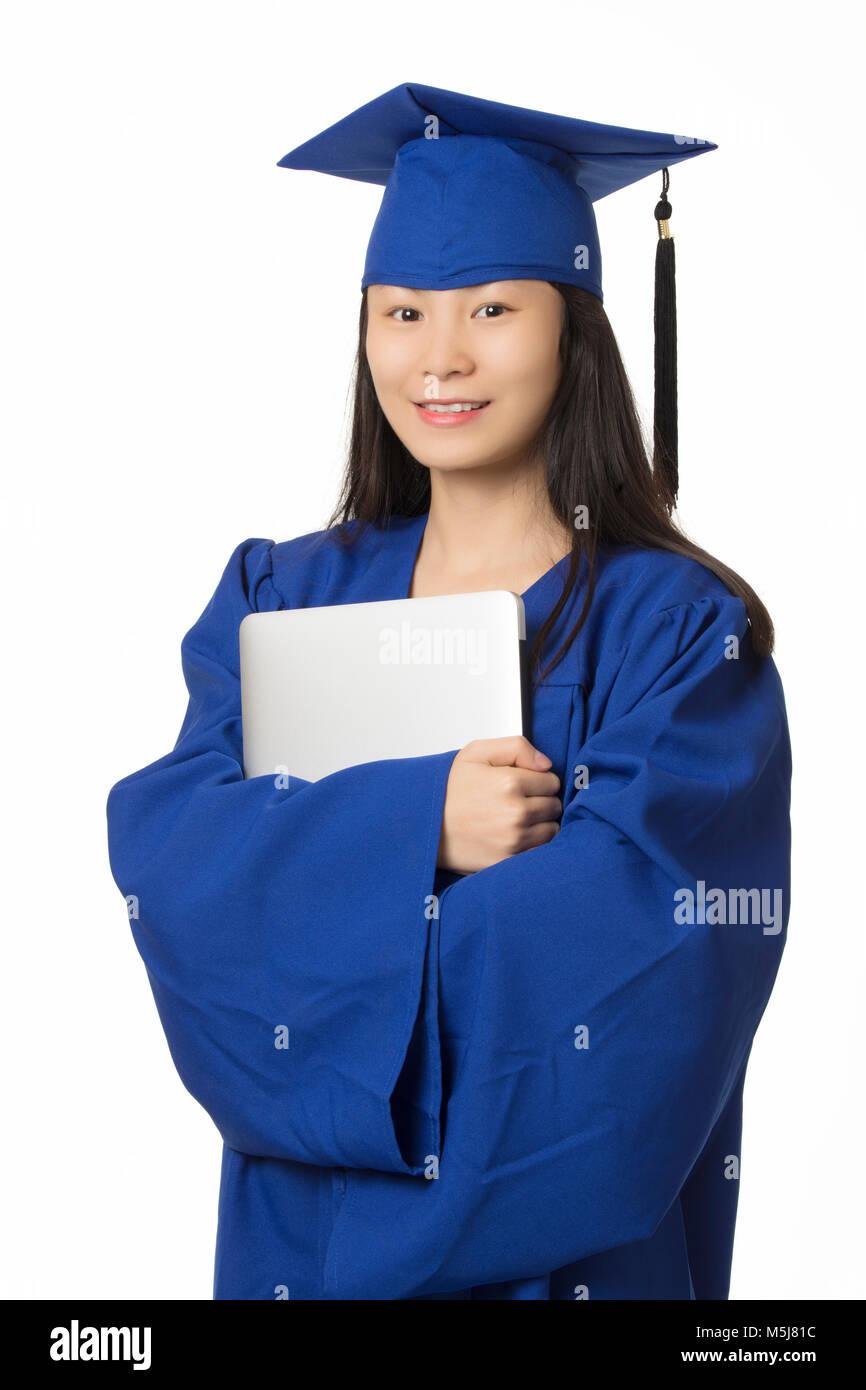 eb8787ca4 Hermosa mujer asiática sosteniendo un ordenador mientras llevaba una toga  de graduación azul aislado sobre Imagen
