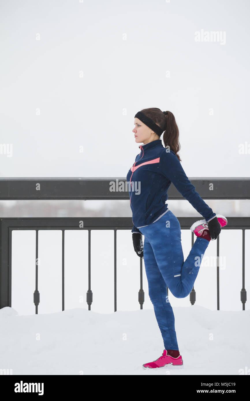 Corredoras haciendo ejercicios de flexibilidad para las piernas antes de ejecutar en la nieve del invierno promenade, Imagen De Stock