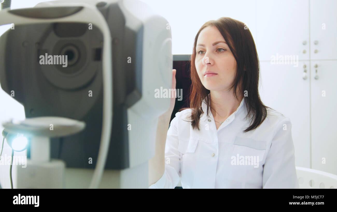Oftalmólogo en ojos clínica realizando un diagnóstico para el paciente - Alta tecnología en Imagen De Stock