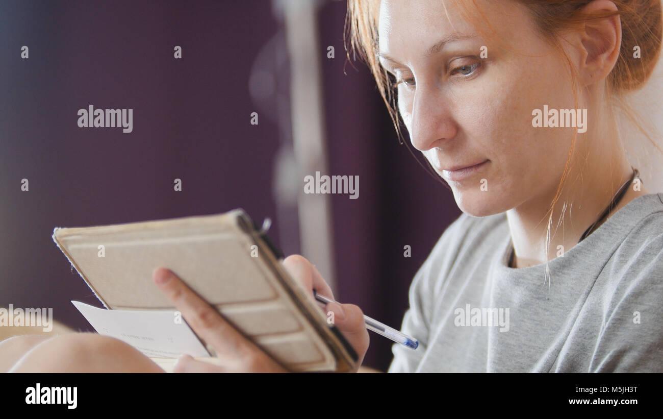 Retrato de una mujer bonita en casa sentado en el sofá y trabajando con portátiles y gadgets Foto de stock