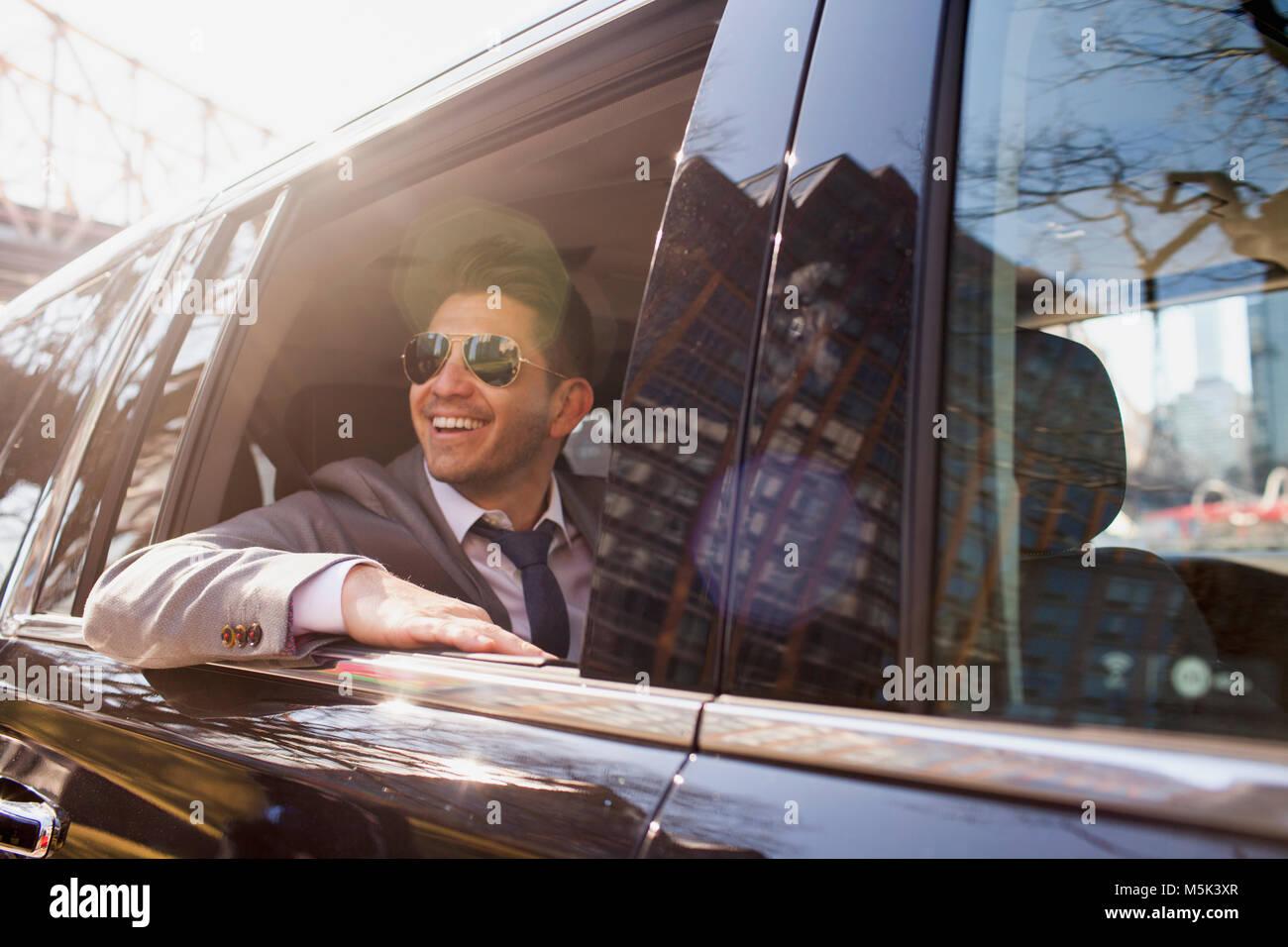 El hombre de negocios joven lookingout la ventana sentado en el coche limousine service Imagen De Stock