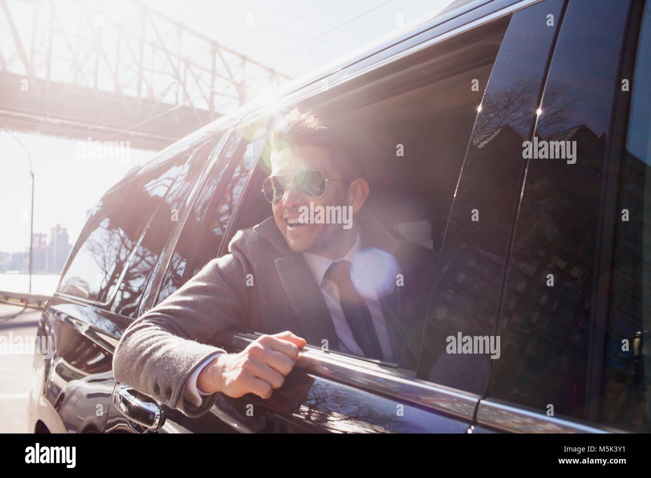 Empresa joven hombre mirando mirando por la ventana sentado en el coche limousine service Imagen De Stock