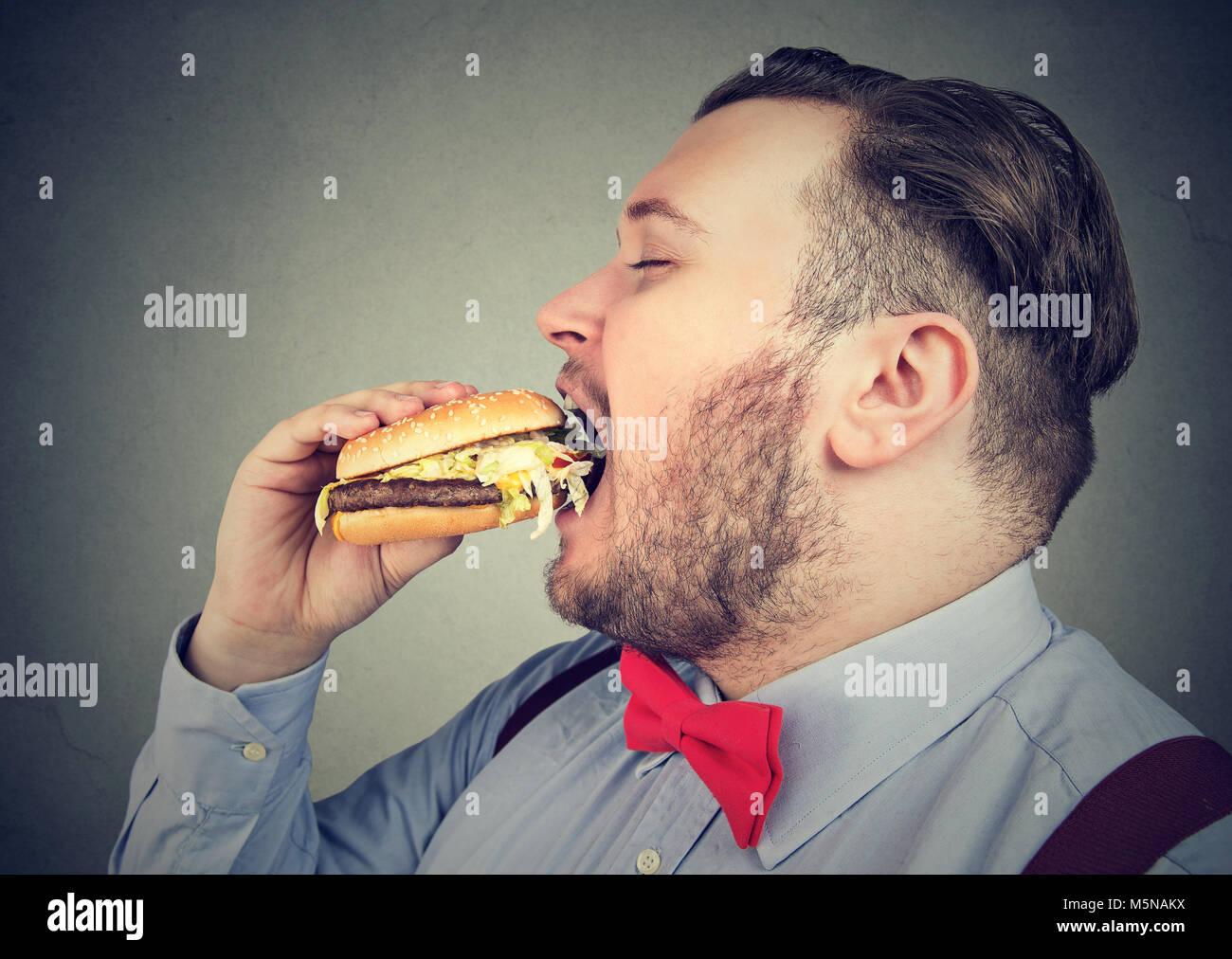 El perfil lateral de un hombre gordo, comer una hamburguesa jugosa. Imagen De Stock