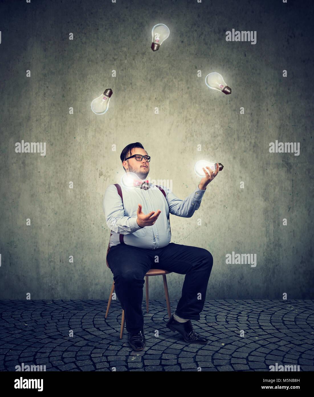 Chubby joven hombre sentado en una silla y malabarismos con bombillas siendo genio. Imagen De Stock