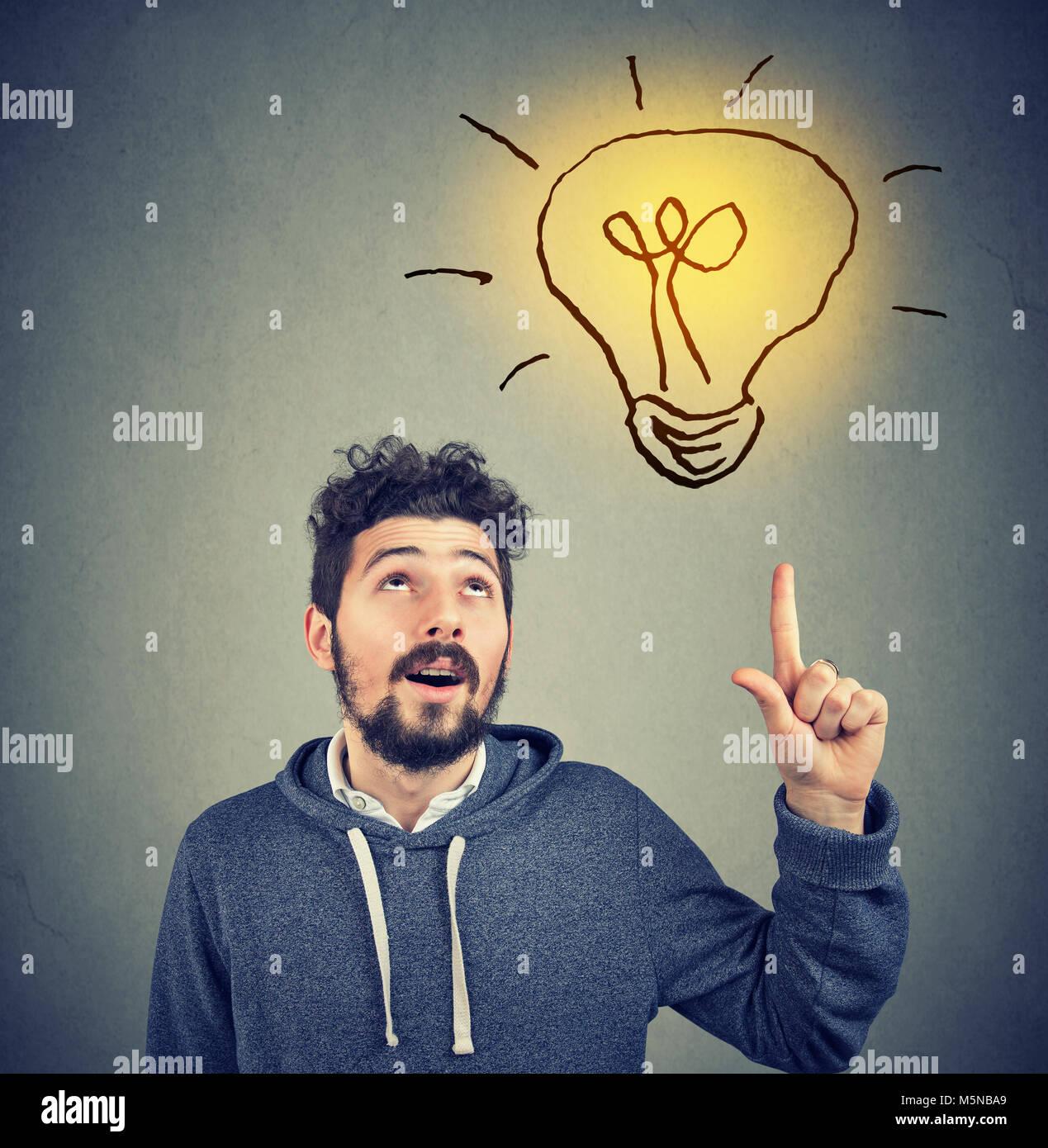 Casual hombre barbado en hoodie apuntando hacia arriba la iluminación con una gran idea. Imagen De Stock