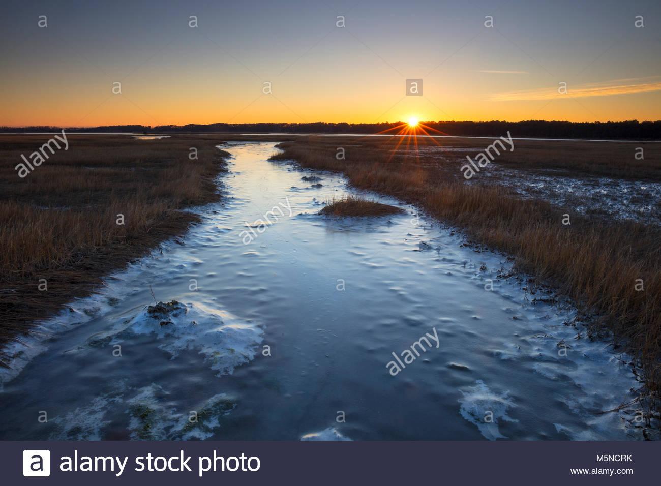 El sol se eleva sobre el Canal Assateague cubiertas de hielo, que separa las islas de Chincoteague y Assateague Imagen De Stock