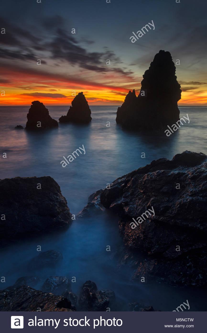 Un espectacular atardecer de colores el cielo detrás de grandes pilas de mar en Rodeo Cove situado en Marin, Imagen De Stock