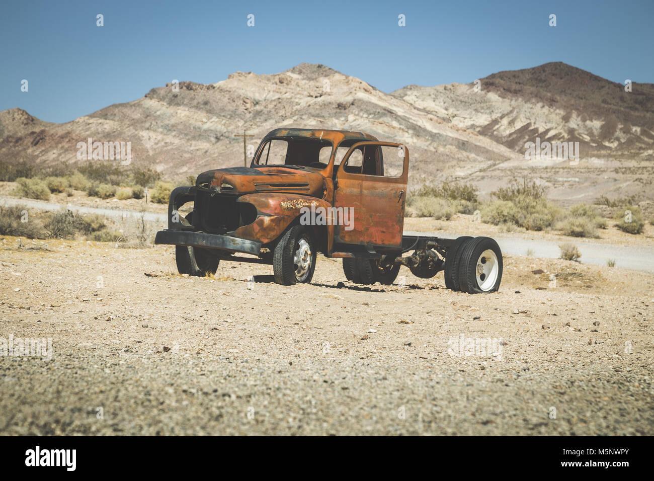 Vista clásica de una vieja camioneta oxidada de un accidente automovilístico en el desierto, en un hermoso día soleado con el cielo azul en verano con filtro vintage retro, EE.UU. Foto de stock
