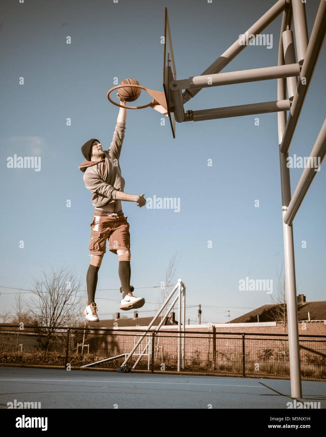 Un rodaje en exteriores de un jugador de baloncesto en Devizes, Wiltshire. Rodada en la luz solar natural en una cancha de baloncesto. Amplia profundidad de archivado, con buena iluminación. Foto de stock