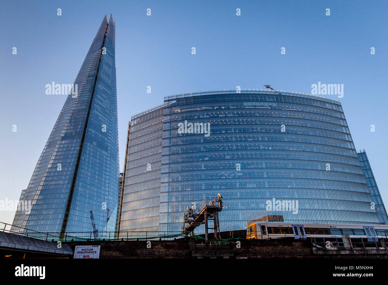 Un tren de cercanías pasa el Shard y el edificio de noticias, London Bridge Quarter, Londres, Reino Unido. Imagen De Stock
