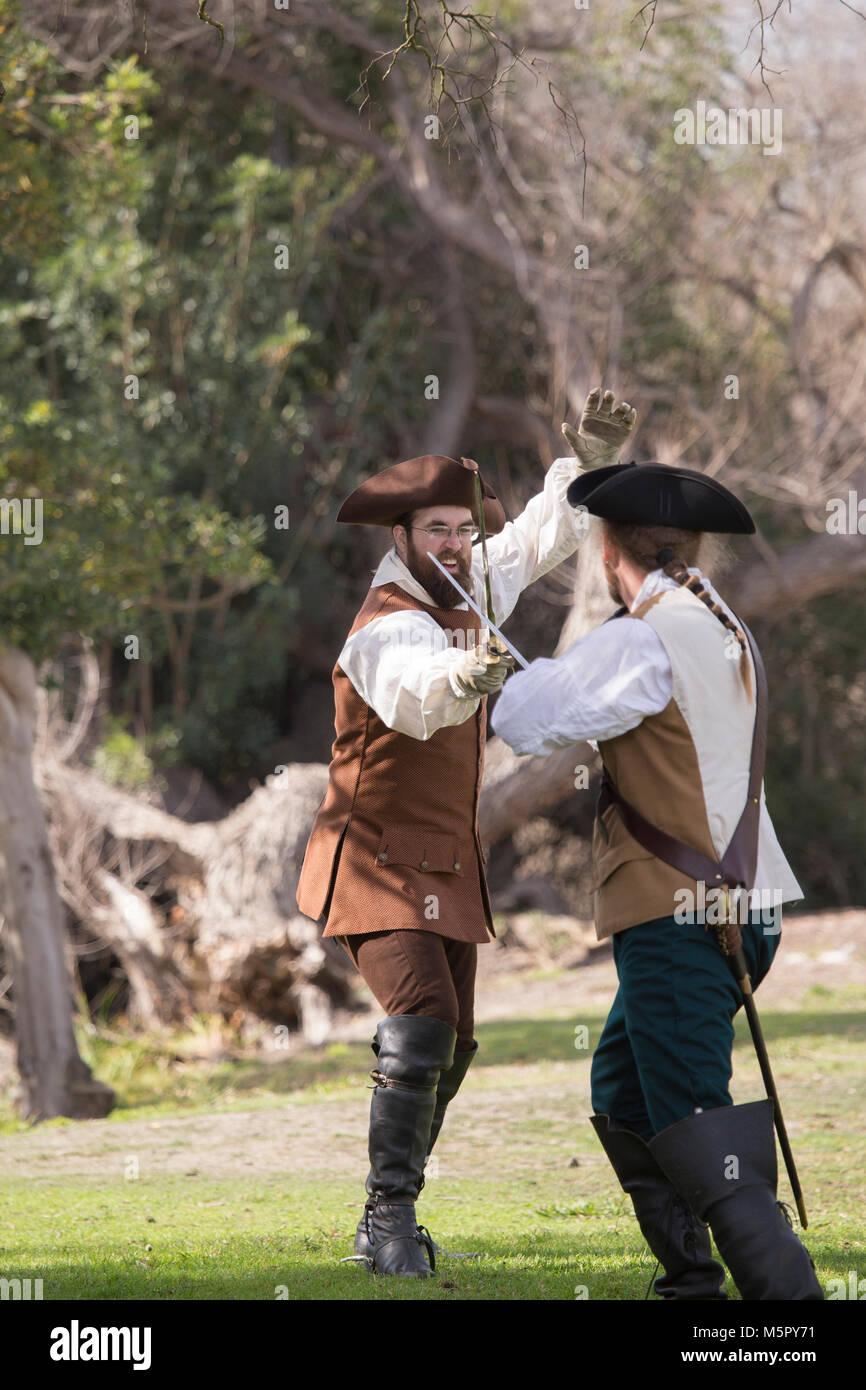 2 hombres practicar esgrima espada en una recreación de la revolución americana en Huntington Beach, California Imagen De Stock