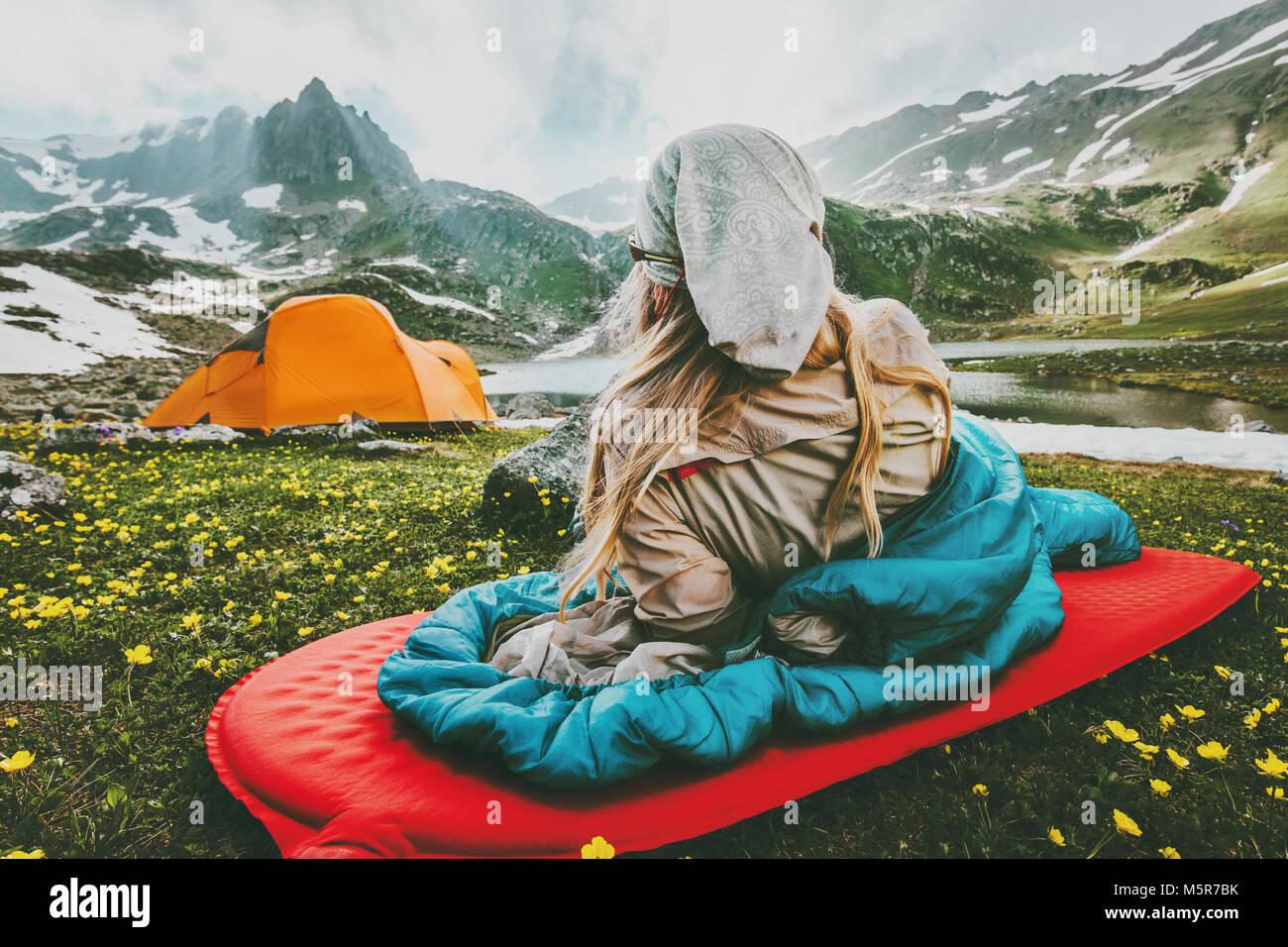 Mujer relajante en saco de dormir sobre la alfombra roja camping vacaciones viajes en montañas concepto de estilo Foto de stock