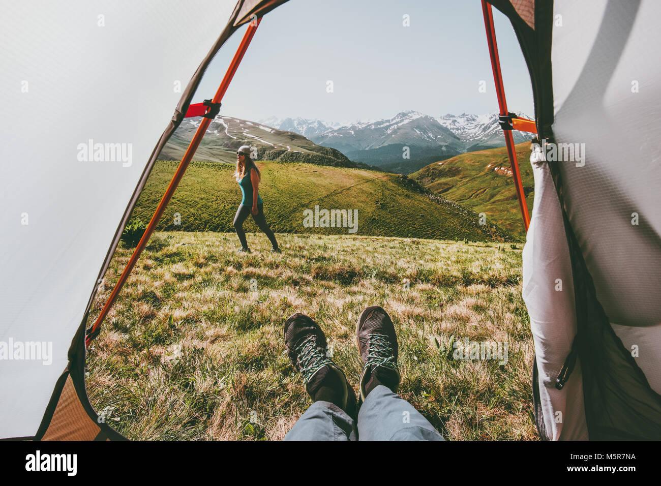 Camping par viajar vista desde la carpa entrada mujer caminando en las montañas hombre pies relajante dentro Imagen De Stock