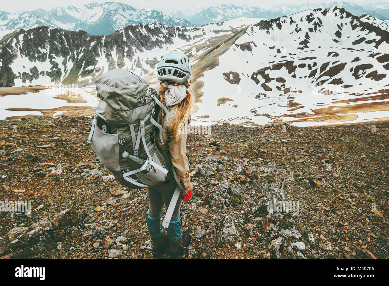 Mujer del viajero con mochila de senderismo en las montañas de viajar concepto de aventura en el estilo de Imagen De Stock