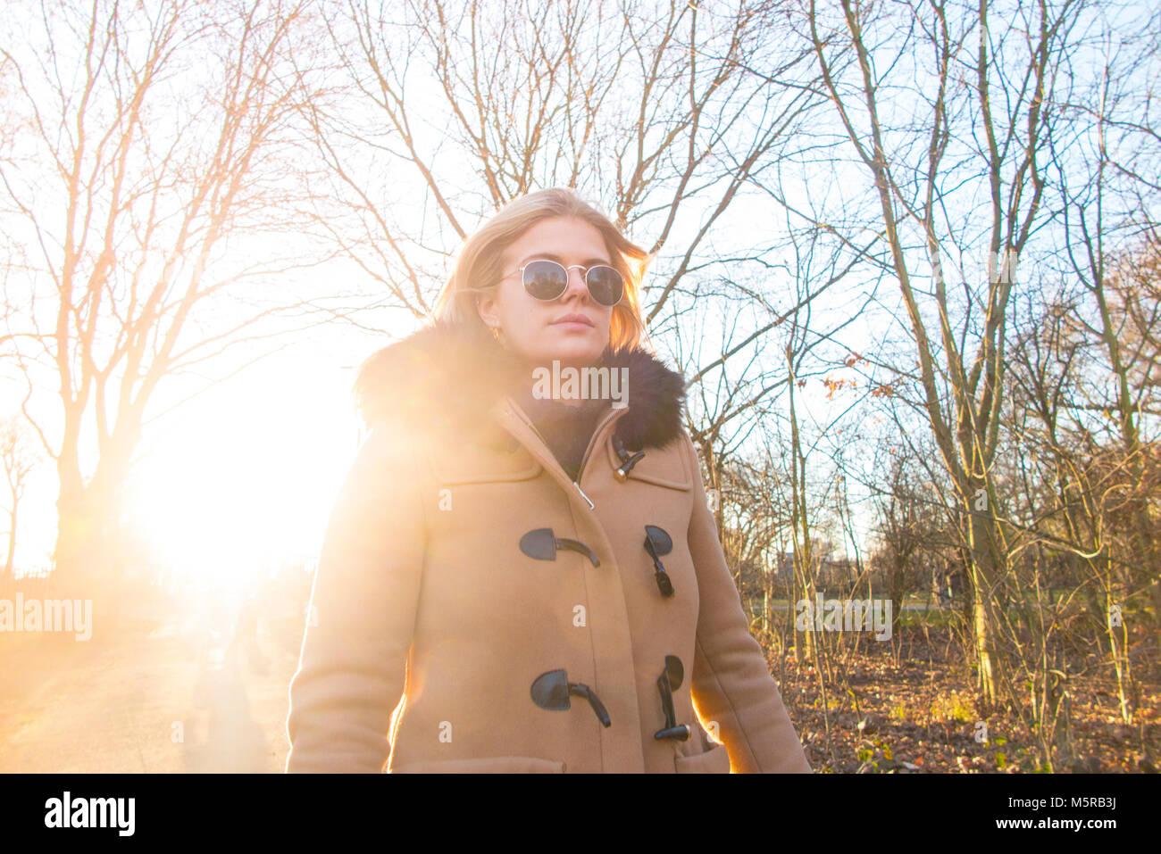 Una chica rubia camina con el sol de invierno Imagen De Stock