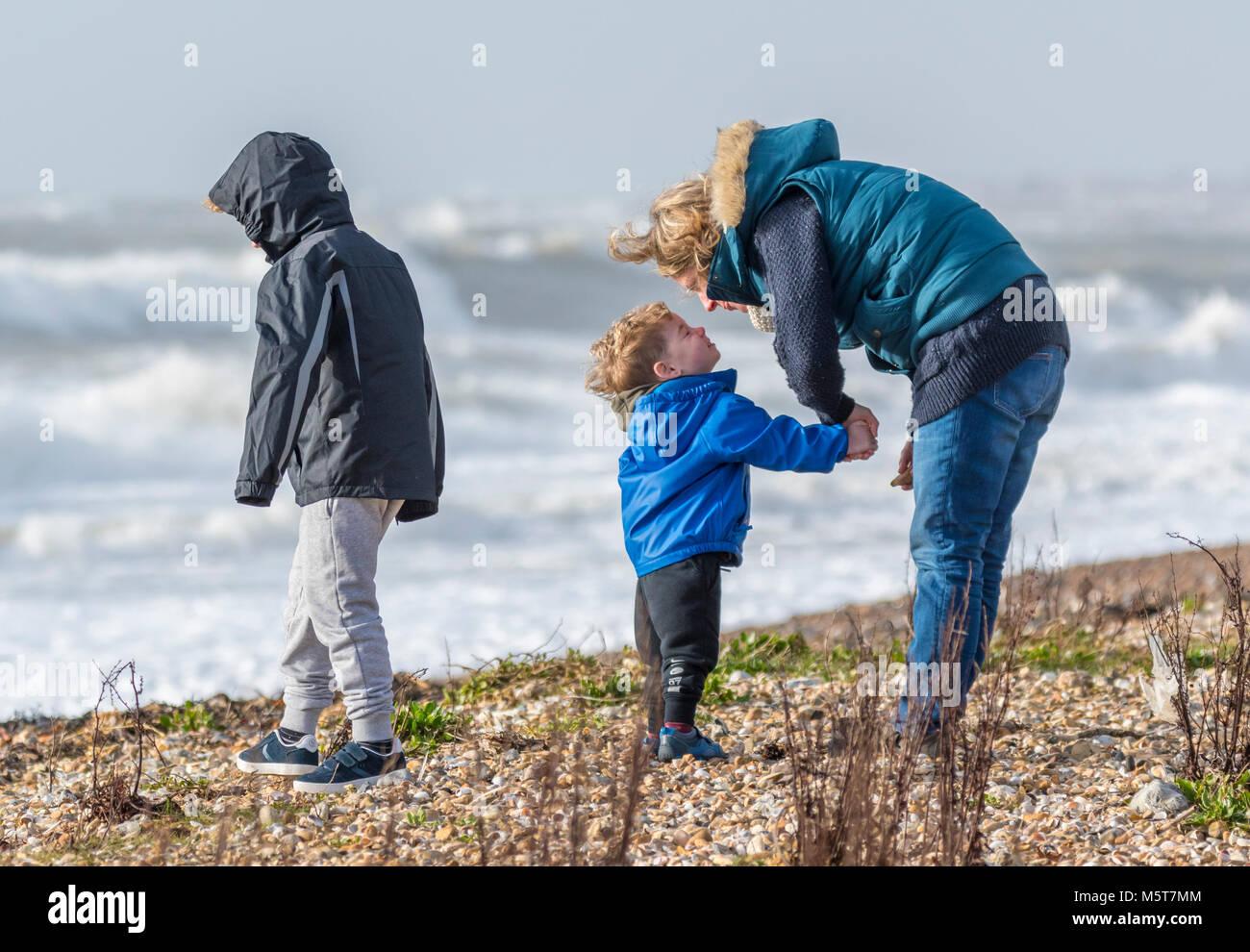 Mujer con 2 niños aparentando ser disciplinar a uno de ellos en una playa en una dura jornada de frío en invierno Foto de stock
