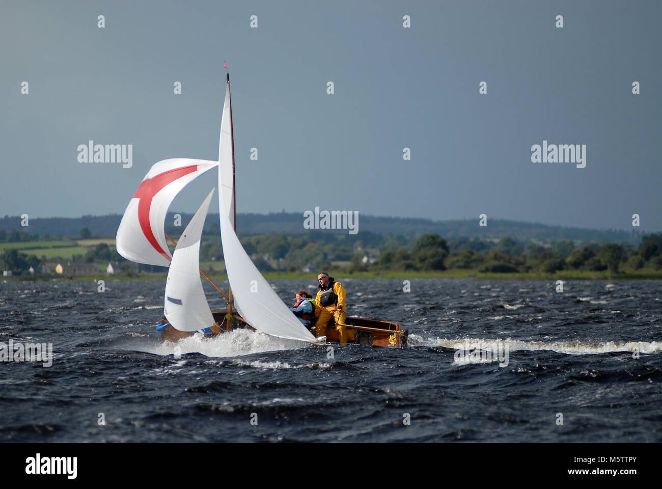 Un tradicional bote Wag agua carreras abajo Lough Ree durante el Irish sailing raid en el río Shannon en Irlanda. El barco está en peligro de naufragio. Foto de stock